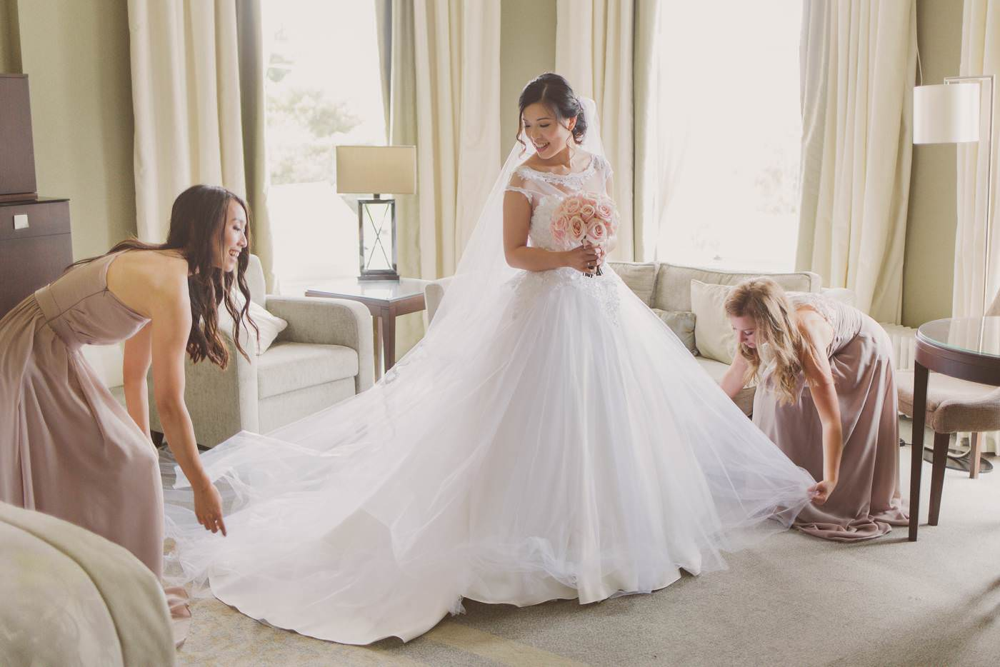 bridesmaids adjust the wedding dress
