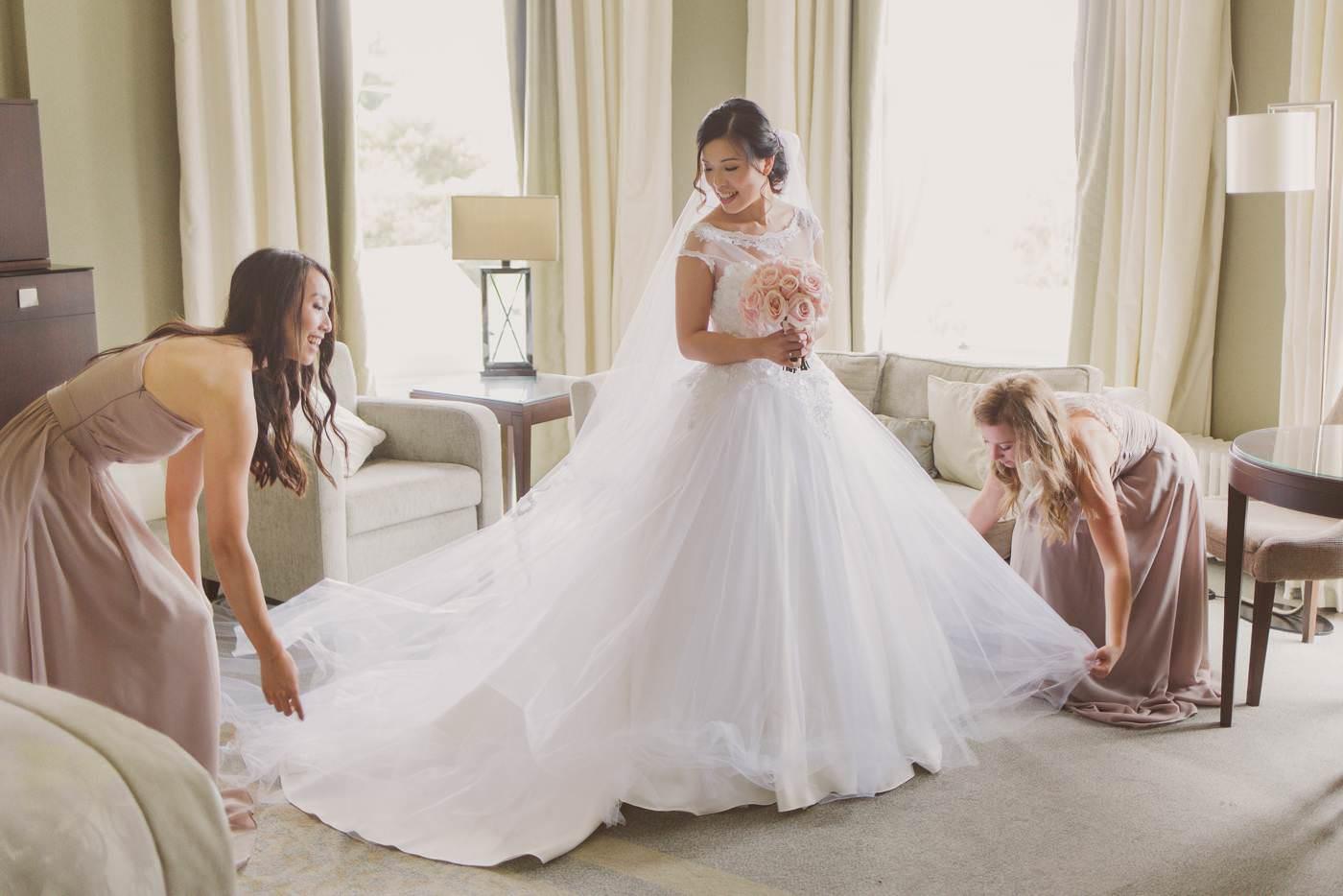 bridesmaids adjust the wedding dress